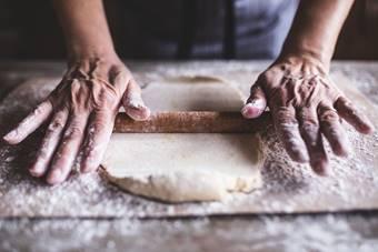 木製の麺棒で生地を延ばす手